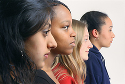 Multiracial group of teenage girls standing alongside each other in profile,