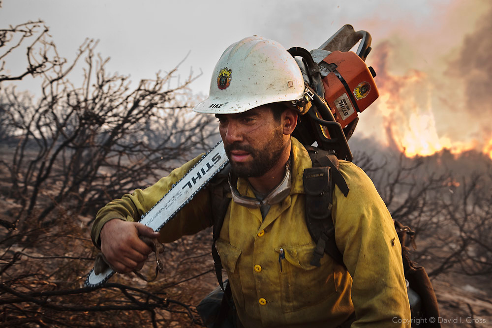 _ Diaz, a sawyer in the Kern Valley Hotshots, carries his 25 lb ( kg) chainsaw up a hill after clearing heavy brush around a spot fire at the La Brea Fire.