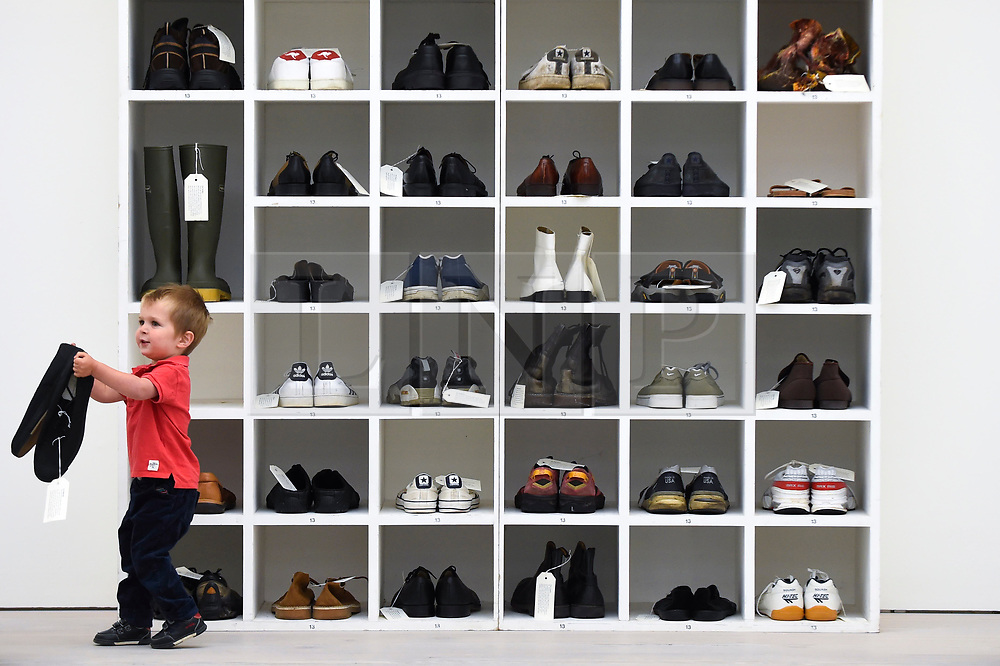"""© Licensed to London News Pictures. 27/09/2018. LONDON, UK. Emlyn Simmonds, aged two and a half, from Lewisham, plays with a pair of size 13 shoes, in front an installation called """"Walk A Mile In My Shoes"""", 2006, by Bedwyr Williams  Preview of """"Black Mirror"""", a major new exhibition featuring the work of 26 contemporary artists, at the Saatchi Gallery.  The show explores art's role in social satire and how political uncertainty has influenced art of recent years and runs 28 September to 13 January 2019.   Photo credit: Stephen Chung/LNP"""