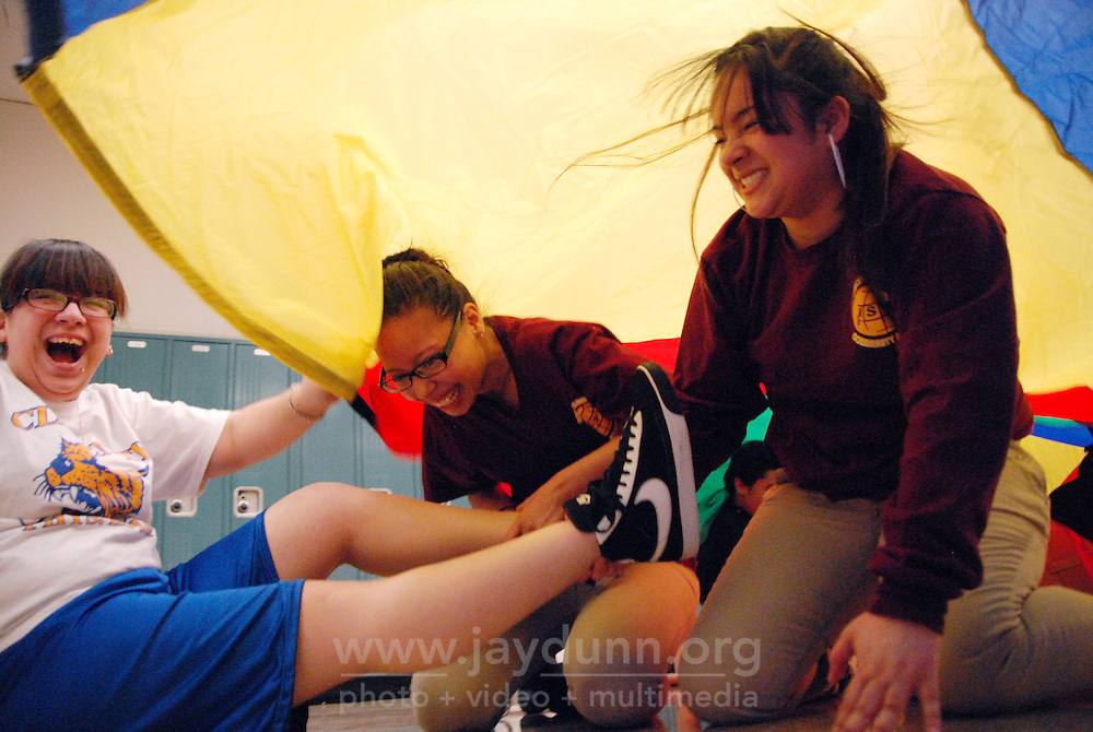 """USA, Chicago, IL, January 19, 2010. Melina Melendez, Lilliana Roman and Atalia Rivera have a good laugh while playing """"Sharks and Lifeguards."""" In its tenth year, the mission of Play for Peace is """"bring together children, youth and organizations from communities in conflict"""" together. The group believes that in cooperative play, laughter is the best medicine, and has proven itself worthy in places as diverse as Guatemala, Northern Ireland, and the Middle East. In practice at Roberto Clemente High School in Chicago's rough-and-tumble Humboldt Park area, students having a Play for Peace """"meeting"""" made remembering people's names' working as a team, encouragement, and partnership a priority in over an hour of flat-out fun. These upbeat, multi-racial students will go on to use their open minds in mentoring younger kids in the spirit of friendship and equality.  Photo for Hoy by Jay Dunn."""
