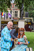 Two people appear to be wearing the fancy outfit as they wait for thousands of youth to participate in an anti-government musical rave in central outside Westminster Palace, Parliament Square in London on Sunday, June 27, 2021. (VX Photo/ Vudi Xhymshiti)