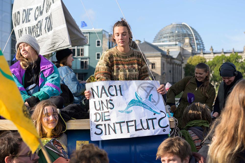 """09 OCT 2019, BERLIN/GERMANY:<br /> Junge Frau mit einem Plakat """"Nach uns die Sintflut?"""", Extinction Rebellion (XR), eine globale Umweltbewegung protestiert mit der Blockade von Verkehrsknotenpunkten fuer eine Kehrtwende in der Klimapolitik, im Hintergrund die Kuppel des Reichstagsgebaeudes, Marschallbruecke<br /> IMAGE: 20191009-02-010<br /> KEYWORDS: Demonstration, Demo, Demonstranten, Klima, Klimawandel, climate change, protest, Marschallbrücke"""
