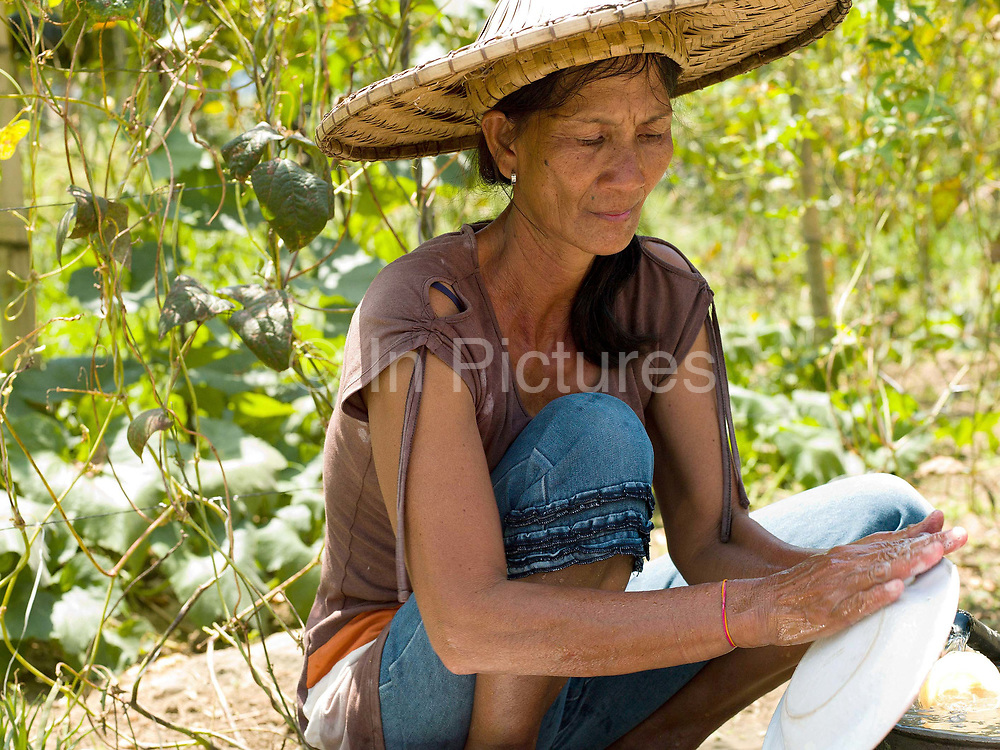 Vegetable and rice farmer, Teodora Ayson washes dishes outside her home in Pamantingan, Esperanza, Sultan Kudarat province, Mindanao Island, The Philippines.