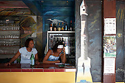 Taking telephone orders near rocket painting at the Délice restaurant in the old quarter of Kourou, French Guiana..