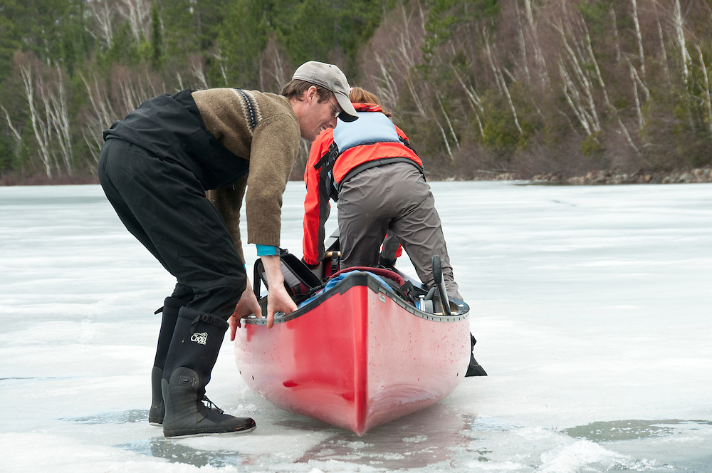 Canoeists propel their boat across ice during an early spring trip at Lady Evelyn-Smoothwater Provincial Park in Ontario Canada.