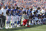 Some Buffalo Bills players stand while others kneel during the playing of the National Anthem before the 2017 NFL week 3 regular season football game against the against the Denver Broncos, Sunday, Sept. 24, 2017 in Orchard Park, N.Y. The Bills won the game 26-16. (©Paul Anthony Spinelli)