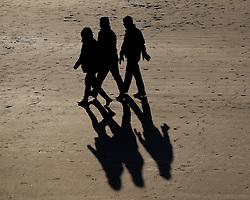 © Licensed to London News Pictures. <br /> 28/12/2014. <br /> <br /> Saltburn, United Kingdom.<br /> <br /> Families enjoy a walk at Saltburn beach on a freezing cold morning on Teesside.<br /> <br /> Photo credit : Ian Forsyth/LNP