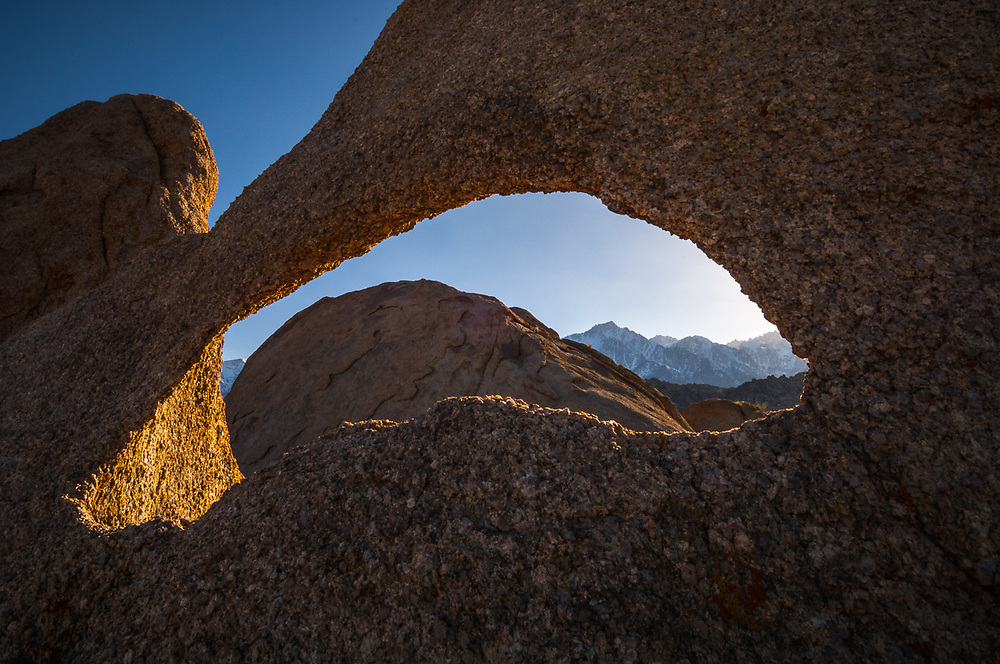 Lone Pine Peak and the eastern Sierra Mountains framed by an eroded window in  a granite boulder, afternoon light, April, view from the Alabama Hills Recreation Area, U.S. Bureau of Land Management, Whitney Portal, Inyo County, California, USA