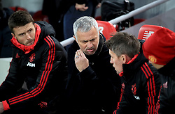 Manchester United manager Jose Mourinho (centre) in the dugout during the Premier League match at Anfield, Liverpool.