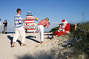 A couple photographing their baby who is being held by a man dressed up as Father Christmas on South Beach Miami