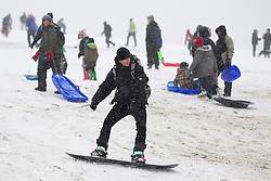© Licensed to London News Pictures. 20/01/2013. London, UK. Londoners take advantage of a snowy Sunday to sledge, and snowboard, down Parliament Hill in Hampstead Heath, London, today 20/01/13) as the capital experienced its third day of heavy snowfall. Photo credit: Matt Cetti-Roberts/LNP