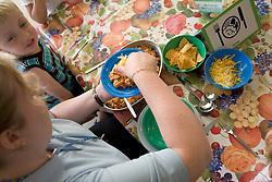 Nursery school Assistant providing lunch for hungry nursery school children,
