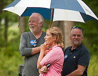 Don Jorgensen, Maggie Hassan and Randy Perkins take refuge under an umbrella as storms pass through during the Merrimack County Democrats BBQ in Canterbury on Sunday afternoon.  (Karen Bobotas/for the Concord Monitor)Merrimack County Democrats backyard BBQ in Canterbury, NH  August 21, 2011.