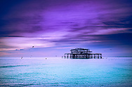 Brighton is a seaside town in the south of England, UK. Dusk on the beach. The West Pier is a pier in Brighton, England. It was designed by Eugenius Birch, opening in 1866 and closing in 1975. The pier was the first to be Grade I listed in Britain but has become increasingly derelict since closure.