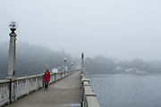 A woman walking across the footbridge across the Pasagassawakeag River in Belfast, Maine.