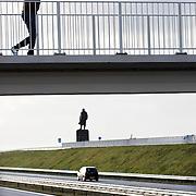 Nederland Den Oever Zurich 22 november 2008 20081122 Foto: David Rozing ..Serie afsluitdijk. De Afsluitdijk is een belangrijke waterkering en verkeersweg in Nederland. De waterkering sluit het IJsselmeer af van de Waddenzee. Hieraan ontleent de dijk zijn naam. De verkeersweg, onderdeel van Rijksweg a7, verbindt Noord-Holland met Friesland...Viaduct naar monument Afsluitdijk, met in de achtergrond Standbeeld van Cornelis Lely, gemaakt door beeldhouwer Mari Andriessen. Cornelis Lely was in 1913 minister van waterstaat en stond aan de wieg van de afsluitdijk.  weg, wegen, snelweg, snelwegen,  deltaplan..Foto David Rozing