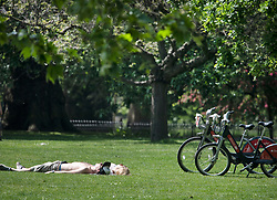 © Licensed to London News Pictures. 09/05/2020. London, UK. A couple sunbathing in St James's Park, central London during lockdown. The government is set to announce measures to ease lockdown, which was introduced to fight the spread of the COVID-19 strain of coronavirus. Photo credit: Ben Cawthra/LNP