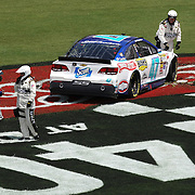 NASCAR Sprint Cup driver A.J. Allmendinger (47) talks with a NASCAR official after crashing on the front stretch during the 56th Annual NASCAR Coke Zero 400 race at Daytona International Speedway on Sunday, July 6, 2014 in Daytona Beach, Florida.  (AP Photo/Alex Menendez)