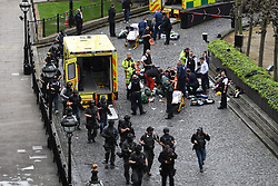 Armed police walk past emergency services attending to a man on the floor (top) and a police officer (centre right) outside the Palace of Westminster, London, after a policeman was stabbed and his apparent attacker shot by officers in a major security incident at the Houses of Parliament.