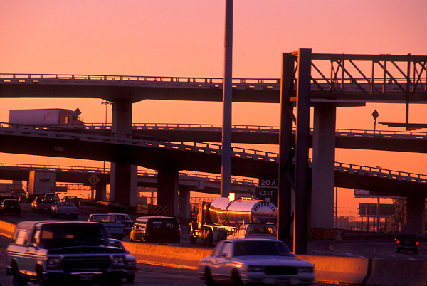 Traffic passing on a Houston freeway in the evening at sunset