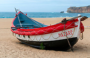 Traditional red, white and blue wooden Portuguese fishing boat on the beach of Nazare, Portugal. These boats are on display by the Dry Fish Museum