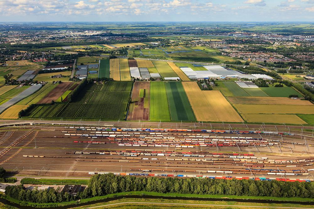 Nederland, Zuid-Holland, Zwijndrecht, 15-07-2012; Kijfhoek, rangeerterrein voor goederentreinen, overzicht van de verdeelsporen. A16 en Hendrik-Ido-Ambacht aan de horizon..Kijfhoek huisvest Keyrail, exploitant Betuweroute en is in beheer bij ProRail. De Betuweroute, die begint als Havenspoorlijn op de Maasvlakte, verbindt via Kijfhoek de Rotterdamse haven met het achterland. Het rangeeremplacement dient voor het sorteren van goederenwagons waarbij gebruik gemaakt wordt van de zwaartekracht, het 'heuvelen': de wagons worden de heuvel opgeduwd, bij het de heuvel afrollen komen ze, door middel van wissels, op verschillende verdeelsporen. Railremmen zorgen voor het automatisch remmen van de wagons. Na het heuvelproces staan de nieuw samengestelde treinen op aparte opstelsporen..Kijfhoek, railway yard used by ProRail and Keyrail (Betuweroute operator). Kijfhoek connects via the Betuweroute (beginning as Havenspoorlijn on the Maasvlakte), through the port of Rotterdam with the hinterland. The shunting yard for sorting wagons makes use of gravity. The new trains are assembled on separate tracks..luchtfoto (toeslag), aerial photo (additional fee required).foto/photo Siebe Swart