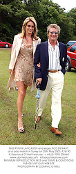 MISS PENNY LANCASTER and singer ROD STEWART, at a polo match in Surrey on 25th May 2003.PJW 90
