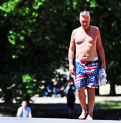 © Licensed to London News Pictures. 13/07/2018<br /> Greenwich, UK.<br /> Hot heat wave weather continues today as the grass in Greenwich Park starts to look like desert sand its so dry.<br /> Half naked and barefoot in the park.<br /> Photo credit: Grant Falvey/LNP