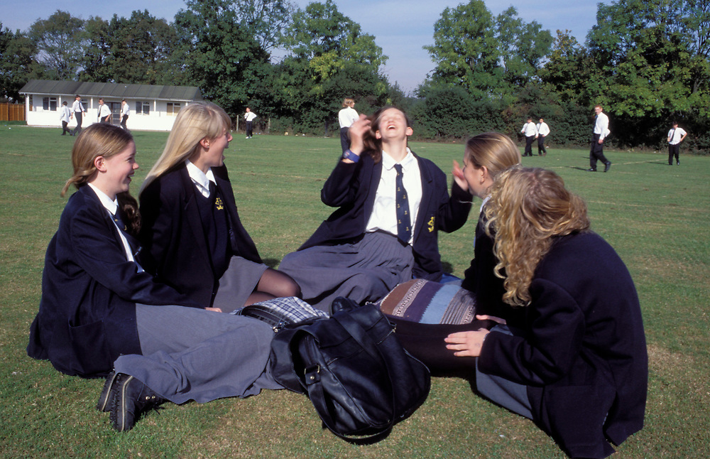 Schoolgirls at breaktime sitting in sports field laughing; secondary school UK