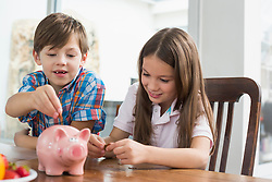 Two children dropping money in piggy bank