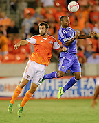 Oct 4, 2013; Houston, TX, USA; Montreal Impact midfielder Collen Warner (18) heads a ball over Houston Dynamo forward Will Bruin (12) during the first half at BBVA Compass Stadium. Mandatory Credit: Thomas Campbell-USA TODAY Sports