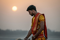 May 18, 2019 - Varanasi, India - On 18 May 2019, an Indian male dressed in traditional clothing performs a sunrise ceremony on the riverbanks of the Ganges River in the city of Varanasi, India. (Credit Image: © Diego Cupolo/NurPhoto via ZUMA Press)