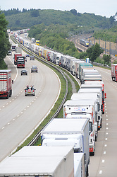 © Licensed to London News Pictures. 28/07/2015<br /> Operation stack lorries between J8 and J9 for Ashford on the M20.<br /> Highspeed Javelin train in pic.<br /> Operation stack is back on the M20 in Kent.<br /> Just days after Operation Stack was taken off the M20, it was brought back in the early hours of this morning.<br /> The authorities are blaming a heavy volume of traffic heading towards the Port of Dover and Eurotunnel and the continued disruption in Calais.<br /> The coast-bound carriageway between junctions 8 and 9 is closed to allow lorries to park, but the slip roads at junctions 9, 10 and 12 and 13 have also been shut. <br /> <br /> (Byline:Grant Falvey/LNP)