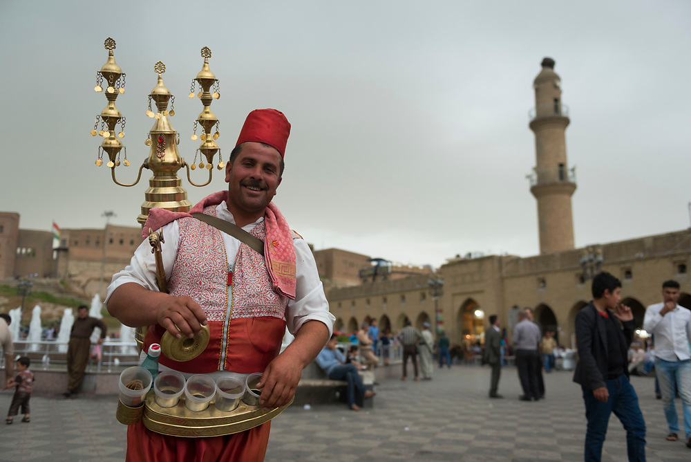 25-year-old Ali Khalil Murat sells tamarind juice late in the afternoon outside the citadel in Erbil, Iraq. Originally from Damascus, Syria, he has lived in Erbil for the past four years.