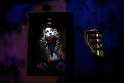 """After a wooden board suddenly fall away from the wall, volunteer, Kiki Goguen, of Brewster, MA, appears as a creepy doll who hands out candy at Chris Baker's haunted house in South Yarmouth, MA. Every year Baker sets up an elaborate Halloween display in his yard and on Halloween, neighborohood residents walk through his frightening """"vortex"""" of horror while trick or treating."""