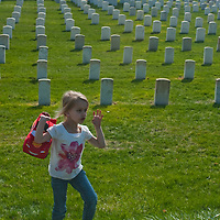 A child plays in the grass at a military cemetary beside Montana's Little Bighorn Battlefield National Monument. Montana