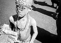 BURMA (MYANMAR) Yangon Division, Yangon, 2006. On the streets of Burma's capital city, Shiva's trident helps a young Hindu boy survive. Yangon receives from the government only a fraction of the electricity it needs to function.