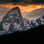 Malachi Artise gets air along a ridge as the clouds glow orange in the Tetons.