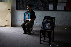 """Zhang Hua Shan, 37, holding a picture of his daughter Zhang Qiu Yue, 12, is seen at Fuxin No.2 Primary  School in Wufu, Sichuan province.  """"The building is dangerous so they moved the older kids to another shool. I want to know why they put the younger children to this builindg."""""""