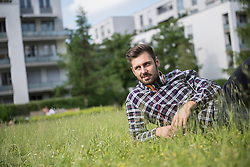 Young man with headphone lying in park, Munich, Bavaria, Germany