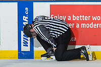 KELOWNA, CANADA - JANUARY 30:  Linesman Cody Wanner grimaces on the ice after being hit with a puck at the Kelowna Rockets against the Seattle Thunderbirds on January 30, 2019 at Prospera Place in Kelowna, British Columbia, Canada.  (Photo by Marissa Baecker/Shoot the Breeze)