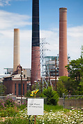 "The sign ""coal Plant in transition"" and sunflowers placed in front of the coal-fired Valmont Power Plant in Boulder, Colorado to protest its continued operation."