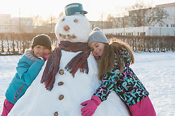 Two girls leaning on snowman