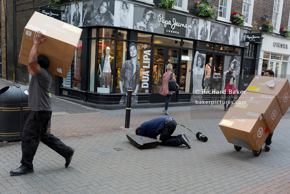 While delivery man take a shipment of boxes to a local address, a workman peers under the pavement during a maintenance job in Carnaby Street, on 5th June 2019, in London, England.