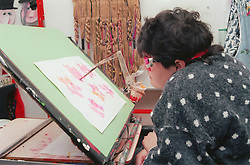 Woman with physical impairment painting using adapted head gear,