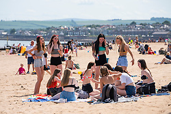 Portobello, Scotland, UK. 24 June, 2020. With sunshine and temperatures of 24C , the beach and promenade at Portobello outside Edinburgh were busy with the public who were enjoying the freedom of a relaxation of the covid-19 lockdown. Iain Masterton/Alamy Live News