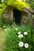 Stone shed in English cottage garden in Swinbrook in The Cotswolds, Oxfordshire, UK
