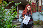 Volunteer Jessica Kleczka poses after posting leaflets for a local community support group called Mutual Aid through letter boxes on a housing estate near the Caledonian Road in North London on 17th March 2020. Mutual Aid and other community support groups have grown significantly in the last few days as people volunteer to help their neighbours who are vulnerable or self isolating with things like shopping, getting prescriptions, and providing meals.  via Getty Images.