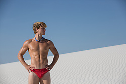 sexy All American man in a bikini bathing suit and goggles by a sand dune