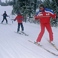 A ski instructor teaches youngsters how to make wedge turns on an easy run at Montana's Big Sky Resort.